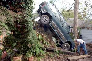 Javier Blas, 20, of Beaumont, Texas, checks out the front end of his Chevy Blazer in the backyard of his Beaumont home. Hurricane Rita left the SUV in a precarious posistion when she blew through the area.  Enterprise file photo