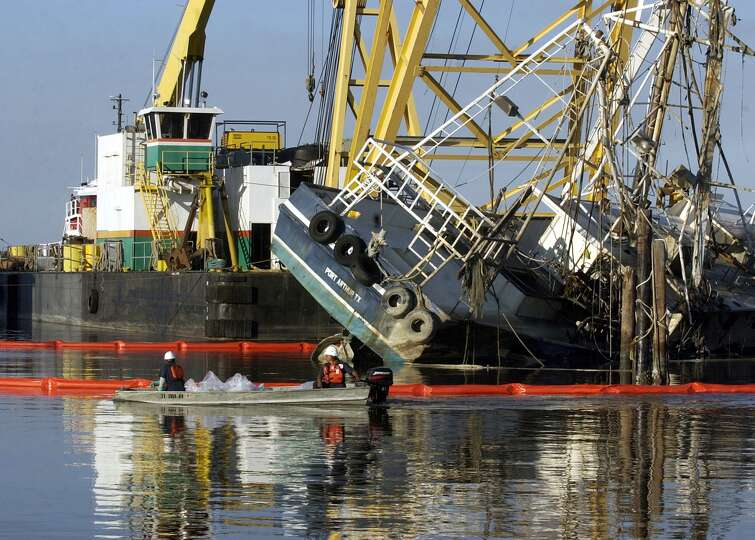 Workers salvage a shrimp boat near the Sabine Pass Port Authority that was partially submerged durin