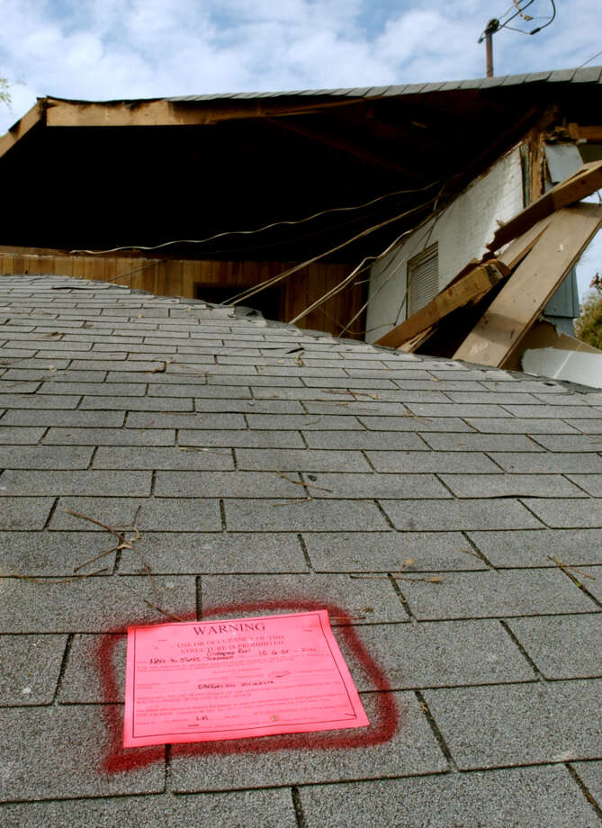 "A ""red tag"" was stapled to the roof, now on the ground, of a home in Sabine Pass, Texas declaring it unlivable. The City of Port Arthur tagged the majority of the homes there. Photo/Jennifer Reynolds"