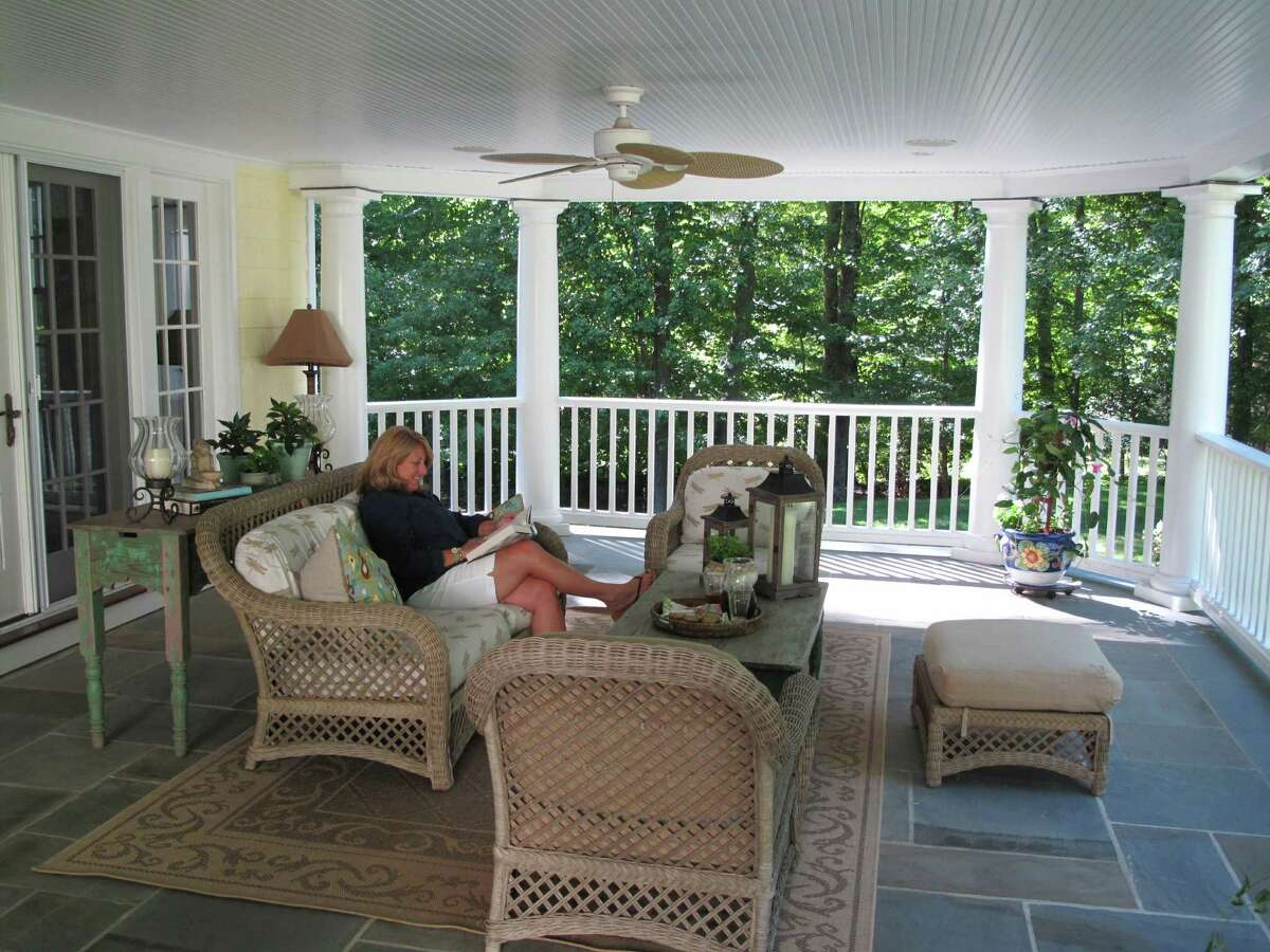 Carol Howe reads a novel on her Alan Lane porch. The family added the rear-facing porch onto the house after renting a vacation home with a porch.