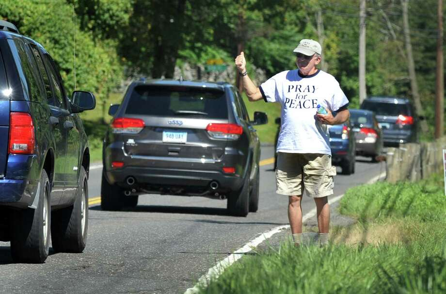 Al Forte, 70, of Stamford, Conn., gave a thumbs-up to passing motorists in Newtown on Wednesday, Sept. 18, 2013, on his walk for peace from Boston to New York City. Forte is on his 11th walk, first inspired by the events of 9/11. This current walk is meant to spread the message of praying for peace. He passed through Stamford on Monday, Sept. 24. Photo: Carol Kaliff / The News-Times