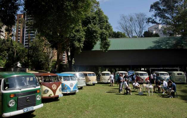 """In this Aug. 25, 2013 photo, members of the Sampa Kombi club, a group ofVolkswagen van owners, gather for their monthly meeting, in Sao Paulo, Brazil. In Brazil the VW van is known as the """"Kombi,"""" an abbreviation for the German """"Kombinationsfahrzeug"""" that loosely translates as """"cargo-passenger van."""" Brazil is the last place in the world still producing the iconic vehicle, or """"bus"""" as it's known by aficionados, but VW says production will end Dec. 31. Safety regulations mandate that every vehicle in Brazil must have air bags and automatic brakes starting in 2014, and the company says it cannot change production to meet the law. Photo: Andre Penner"""