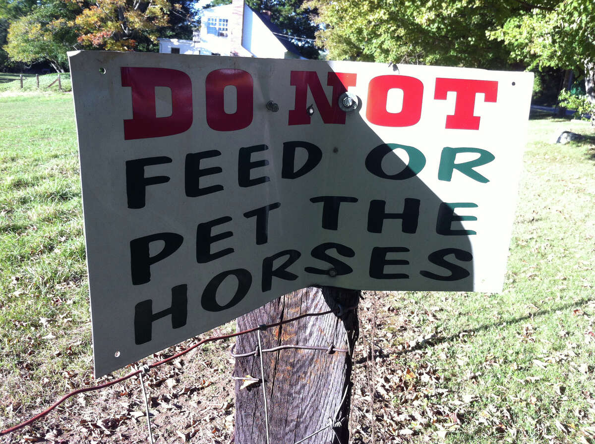One of the several signs along the fence at Glendale Farms in Wheelers Farms Road in Milford urging visitors to steer clear of the horses. The Supreme Court will hear arguments on a lower court ruling defining all horses as