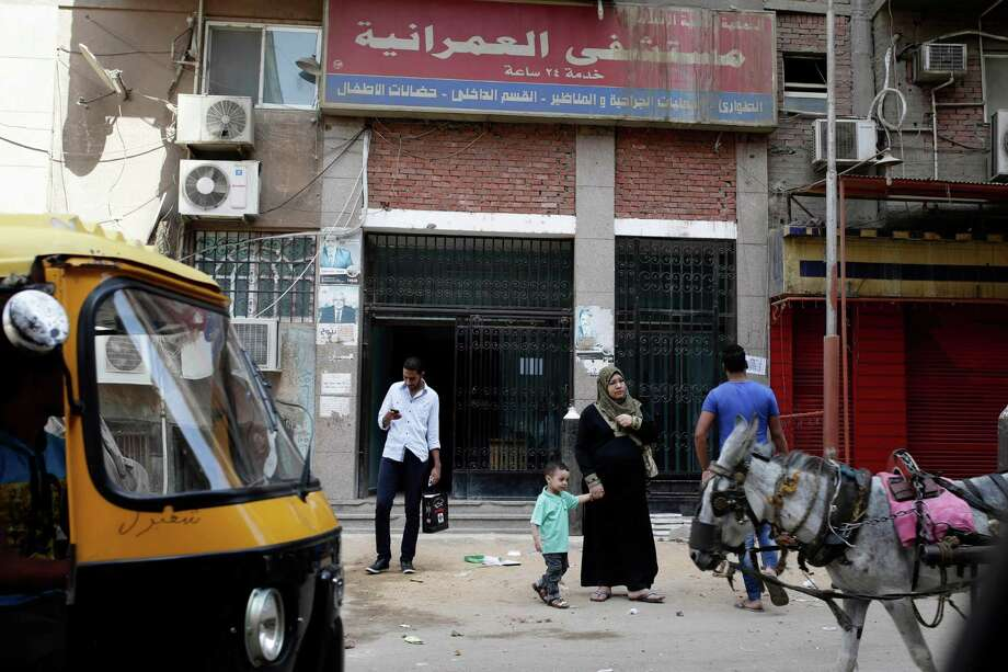 In this Saturday, Sept. 21, 2013 photo, Egyptians walk in front of Al-Omraniyah hospital, run by the Muslim Brotherhood's Islamic Medical Associoation, in Cairo, Egypt. An Egyptian court ordered a ban of the Muslim Brotherhood and confiscation of its assets Monday, Sept. 23, 2013, opening the door for authorities to dramatically accelerate a widescale crackdown. Egypt's military-backed leaders have gone beyond arresting the group's leaders to try to strike a more longterm blow, targeting its extensive network of schools, hospitals, mosques and other social institutions that made it the country's strongest political power. (AP Photo/Hassan Ammar) Photo: Hassan Ammar, STF / AP