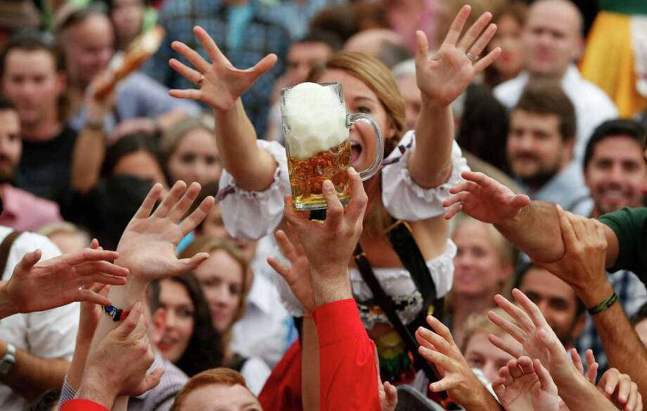 """People celebrate the opening ceremony in the """"Hofbraeuzelt' beer tent of the 180th Bavarian """"Oktoberfest"""" beer festival in Munich, southern Germany, Saturday, Sept. 21, 2013. The world's largest beer festival, to be held from Sept. 21 to Oct. 6, 2013 will attract more than six million guests from around the world. Photo: AP"""