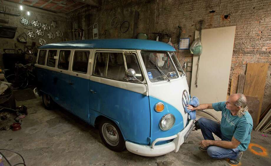 Enio Guarnieri cleans the emblem of his 1972 Volkswagen van in Sao Paulo, Brazil. VW says production of the famous vans will end Dec. 31. Photo: Andre Penner, STF / AP