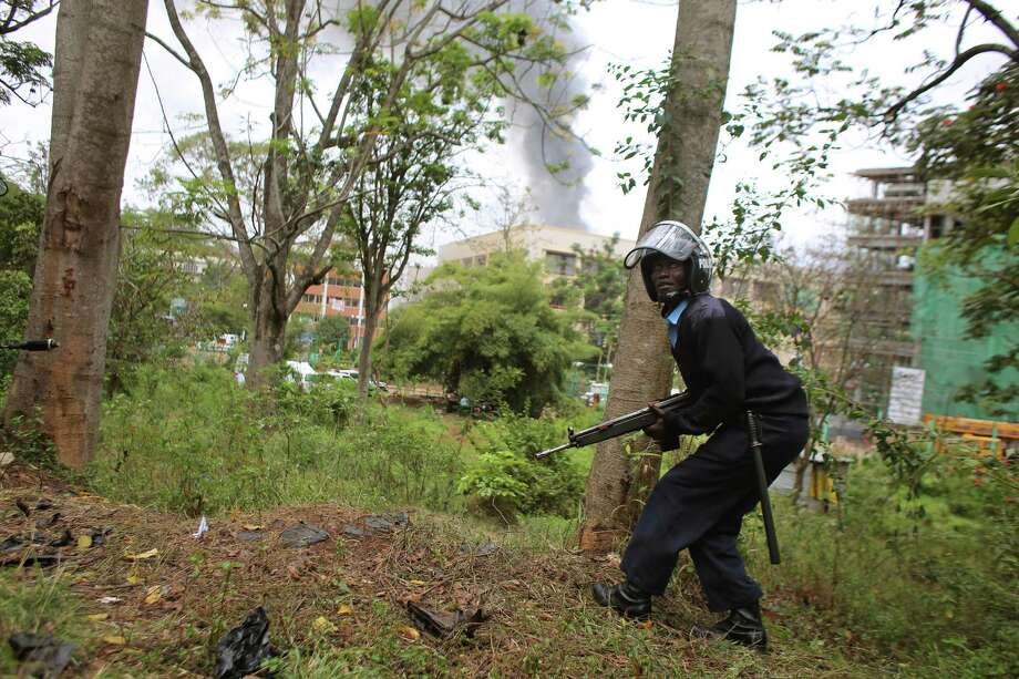 A Kenyan security officer takes cover as smoke rises from the Westgate Mall in Nairobi. Multiple large blasts rocked the mall on Monday, the siege's third day. Photo: Jerome Delay, STF / AP