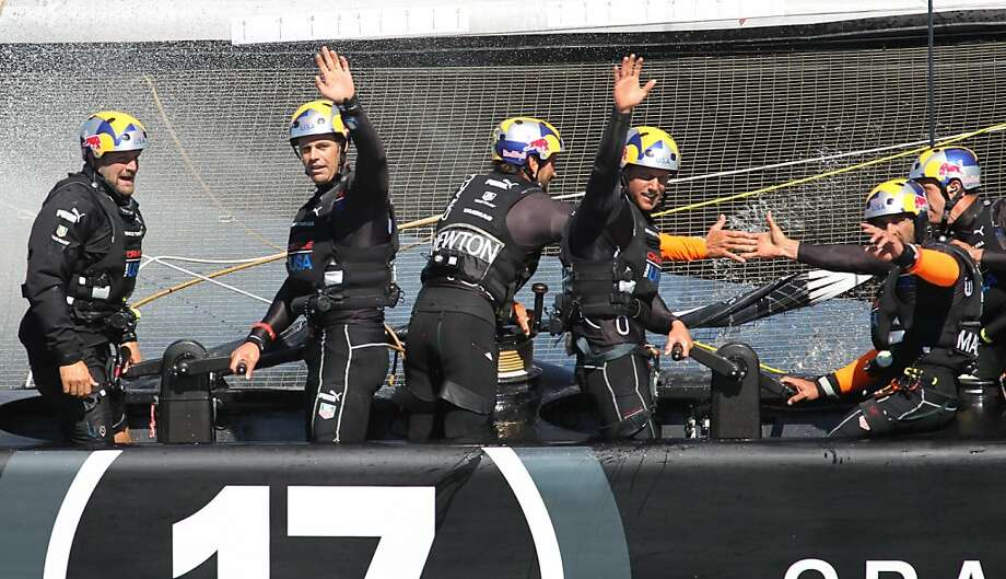 Oracle Team USA sailors wave to fans Monday after winning their fifth straight America's Cup race. Photo: Mathew Sumner, Special To The Chronicle