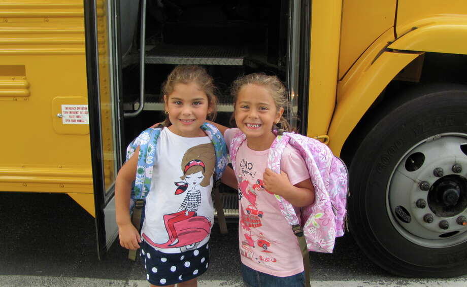 Sofia and Alessandra pose before their bus on their first day of kindergarten, two of the many kids with smiling faces that started their first year this month. (Stella Conti, Colonie)