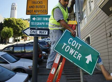 Rick Collaco, right, hands a sign to Mario Mendieta at the corner of Filbert Street and Grant Avenue on September 18, 2013 in the Telegraph Hill area of San Francisco, Calif. Collaco and Mendieta, who are both 7457 sign workers, were installing additional signage to the area around Coit Tower.