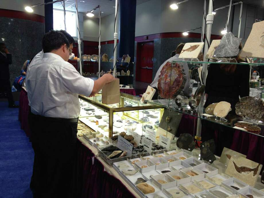Visitors peruse merchandise at the booth of exhibitor IKON, which sells mineral-based jewelry at geological trade shows.