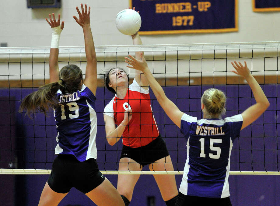 Greenwich's Mirei Kato spikes the ball past Westhill's Adriana Gambino, left, and Stephanie Roones during their game at Westhill High School in Stamford, Conn., on Monday, Sept. 23, 2013. Greenwich won, 3-0. Photo: Jason Rearick / Stamford Advocate