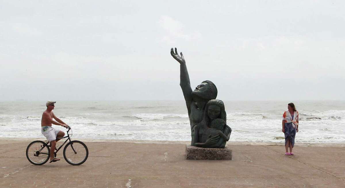Greg Cutler left,rides his bicycle near David W. Moore's bronze sculpture for the victims and survivors of the 1900 Storm on Seawall Boulevard as Kim Locatelli right, looks on, Monday, Sept. 23, 2013, in Galveston.