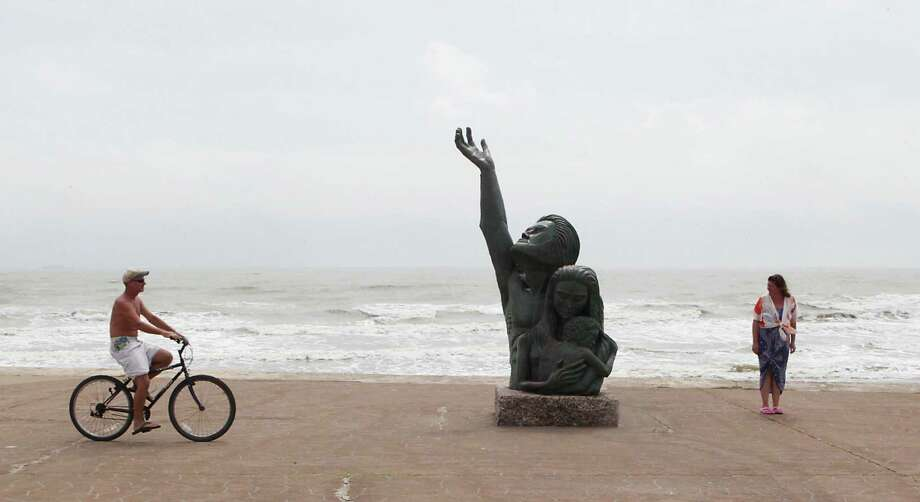 Greg Cutler left,rides his bicycle near David W. Moore's bronze sculpture for the victims and survivors of the 1900 Storm on Seawall Boulevard as Kim Locatelli right, looks on, Monday, Sept. 23, 2013, in Galveston. Photo: James Nielsen, Houston Chronicle / © 2013  Houston Chronicle