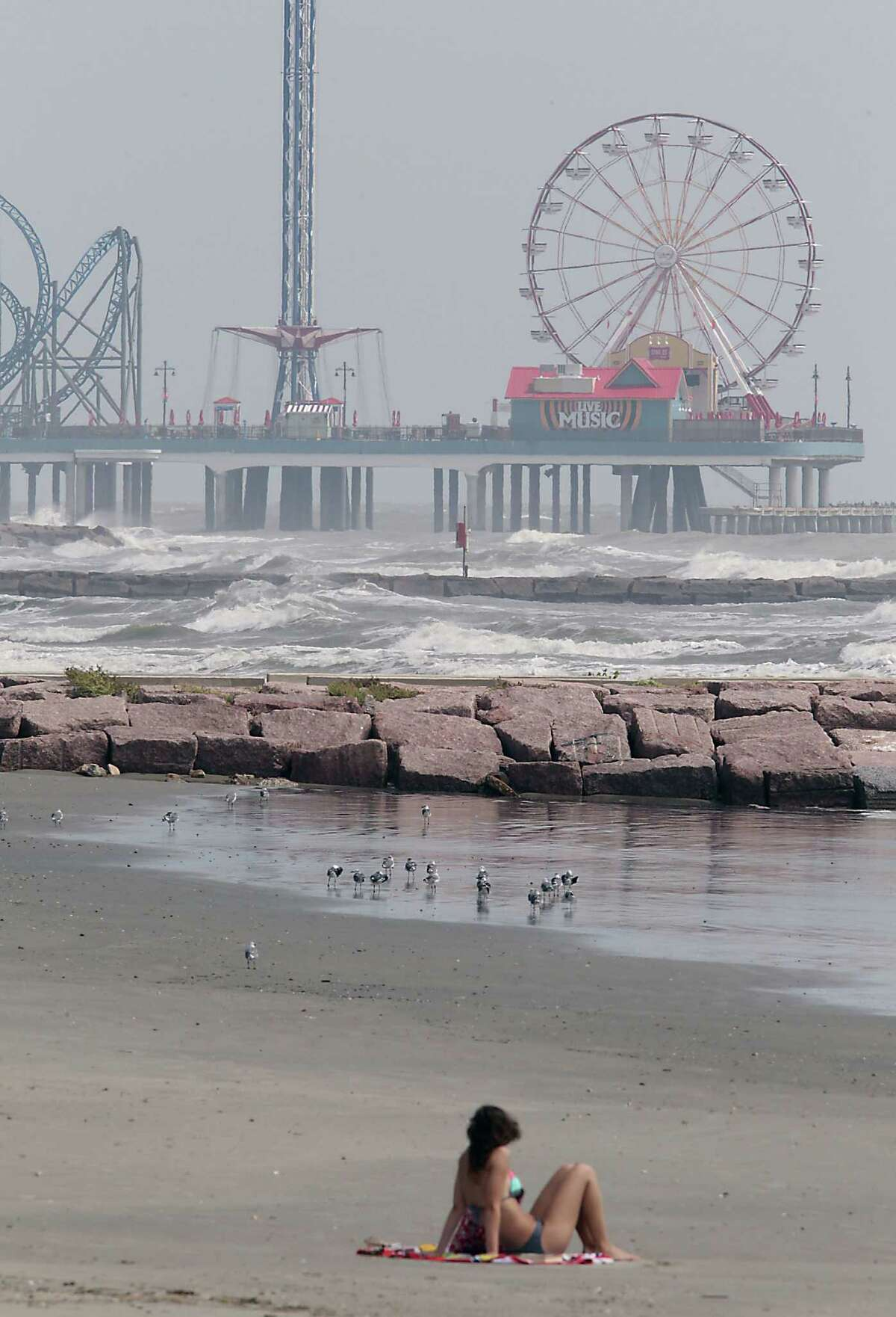 Elizabeth Pruente of Dallas, Texas looks out onto Gulf of Mexico while sitting on the beach Monday, Sept. 23, 2013, in Galveston.