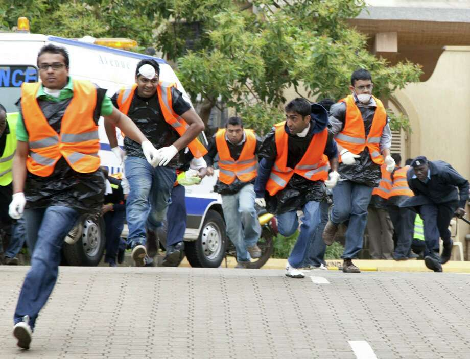 Paramedics and police officers run outside Westgate Mall in Nairobi after heavy shooting started Monday. Kenyan officials subsequently said there were no more civilians trapped inside. Photo: Sayyid Azim / Associated Press