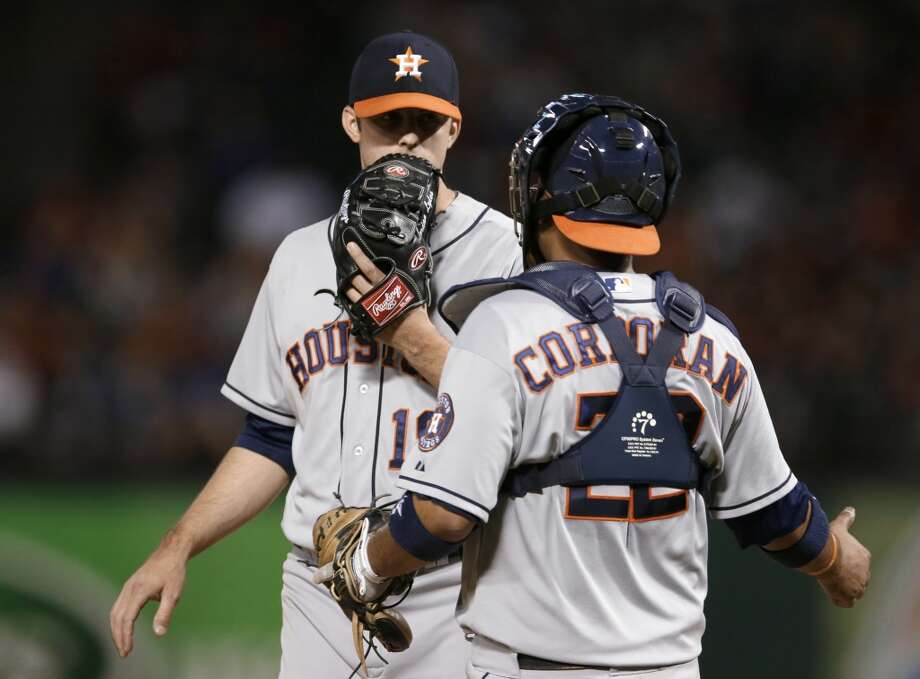 Astros pitcher Jordan Lyles speaks with catcher Carlos Corporan while playing the Rangers. Photo: Tony Gutierrez, Associated Press