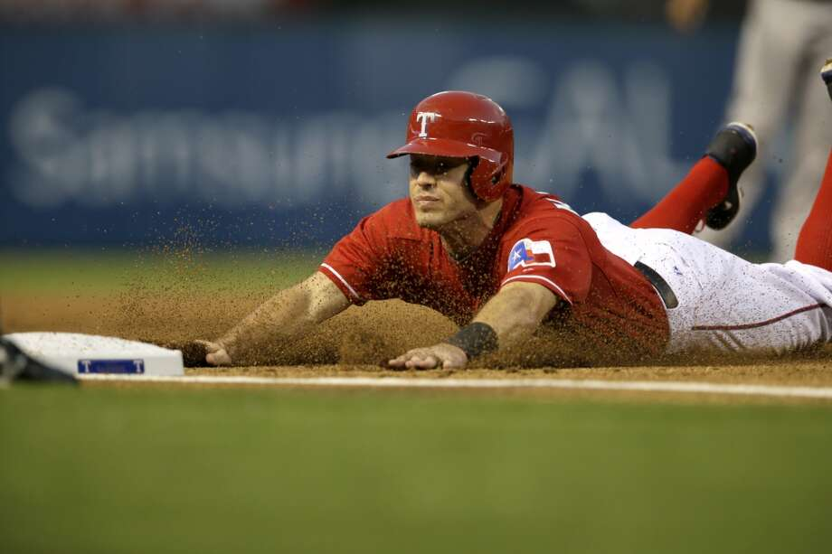 Ian Kinsler of the Rangers slides safely against the Astros. Photo: Tony Gutierrez, Associated Press