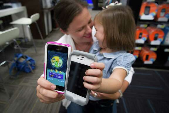 Christen Ramo compares her phone with daughter Isabel's last week at a Best Buy in Atlanta. Isabel has an iPhone 4, and her mom has the new iPhone 5s.