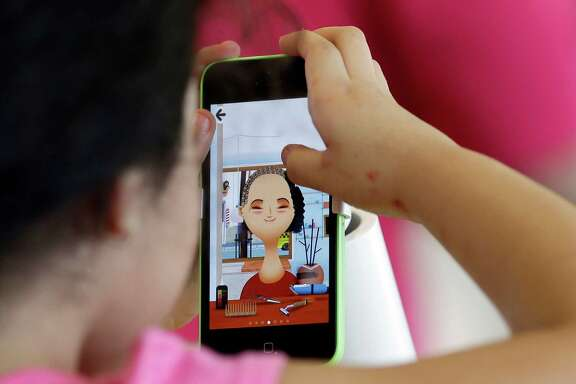 A young girl plays a game on the new iPhone5c during the first day of sales of the iPhone 5s and iPhone 5C, Friday, Sept. 20, 2013, in Hialeah, Fla.