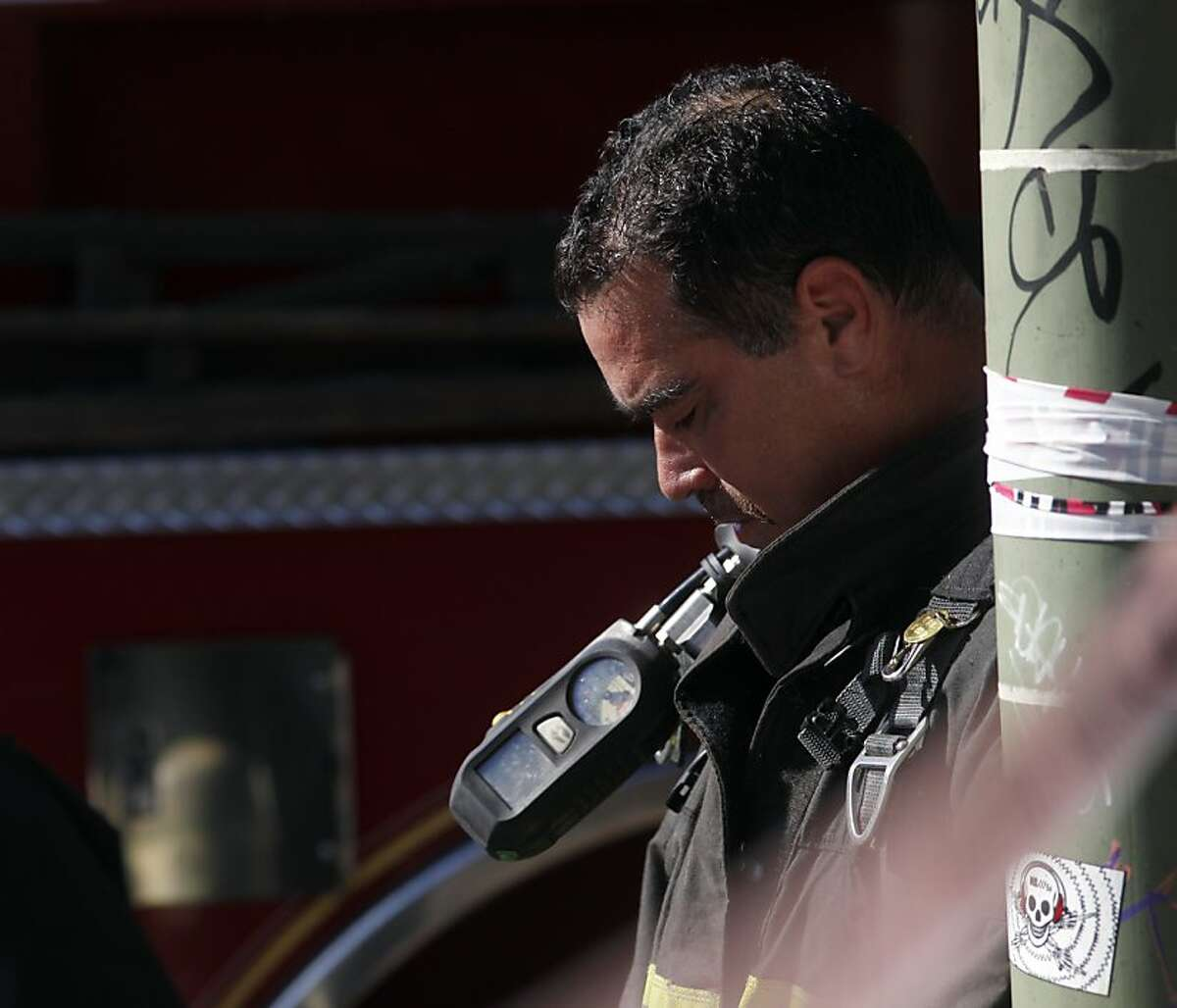 A fire fighter from the Oakland Station 20 catches his breath after coming out of the fire at the Zion's First Church of God in Christ, Monday September 23, 2013, in Oakland, Calif.