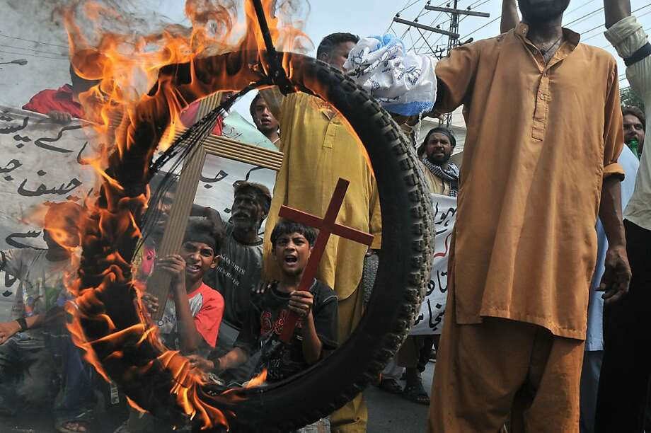 Pakistani Christians hold a burning tyre as they stage a protest in Lahore on September 23, 2013, against the suicide bombing of a church in Peshawar. The death toll from a double suicide bombing on a church in Pakistan rose to 81, as Christians protested across the country to demand better protection for their community.  AFP PHOTO/Arif ALIArif Ali/AFP/Getty Images Photo: Arif Ali, AFP/Getty Images