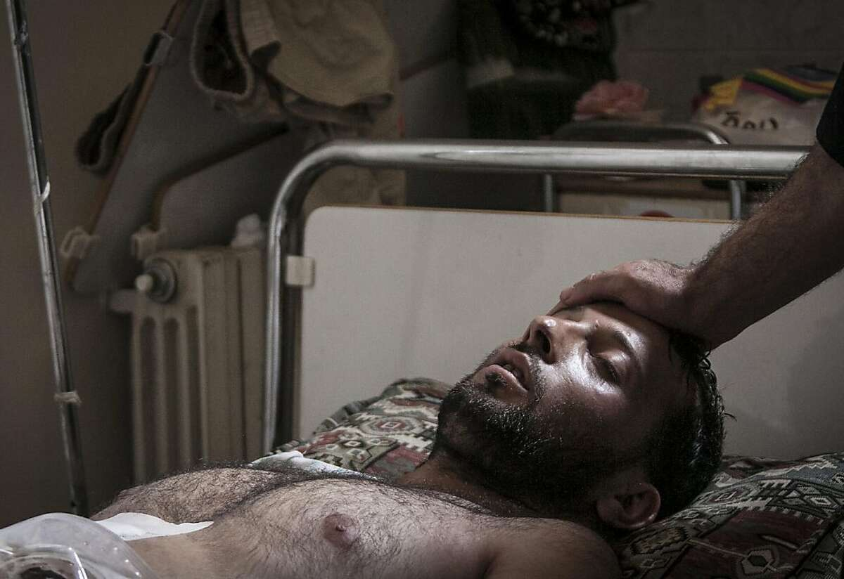 In this Sunday, Sept. 22, 2013 photo, a Syrian doctor touches the forehead of a wounded Free Syrian Army fighter laying on a bed at a field hospital in a village turned into a battlefield with government forces in Idlib province, northern Syria. (AP Photo)