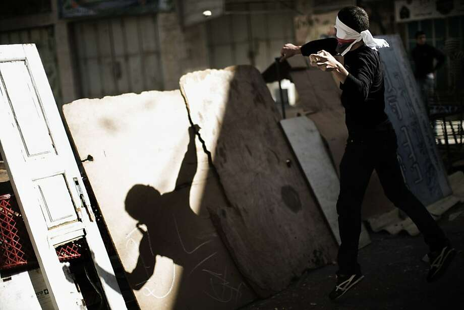 A Palestinian stone thrower stands behind a makeshift barricade as he lobs stones towards Israeli soldiers during clashes in the southern West bank city of Hebron on September 23, 2013, as tensions run high following the death of an Israeli soldier who was shot by a suspected Palestinian gunman. Troops locked down Hebron with roadblocks in the hunt for the gunman, eyewitnesses said. TOPSHOTS/AFP PHOTO/MARCO LONGARIMARCO LONGARI/AFP/Getty Images Photo: Marco Longari, AFP/Getty Images