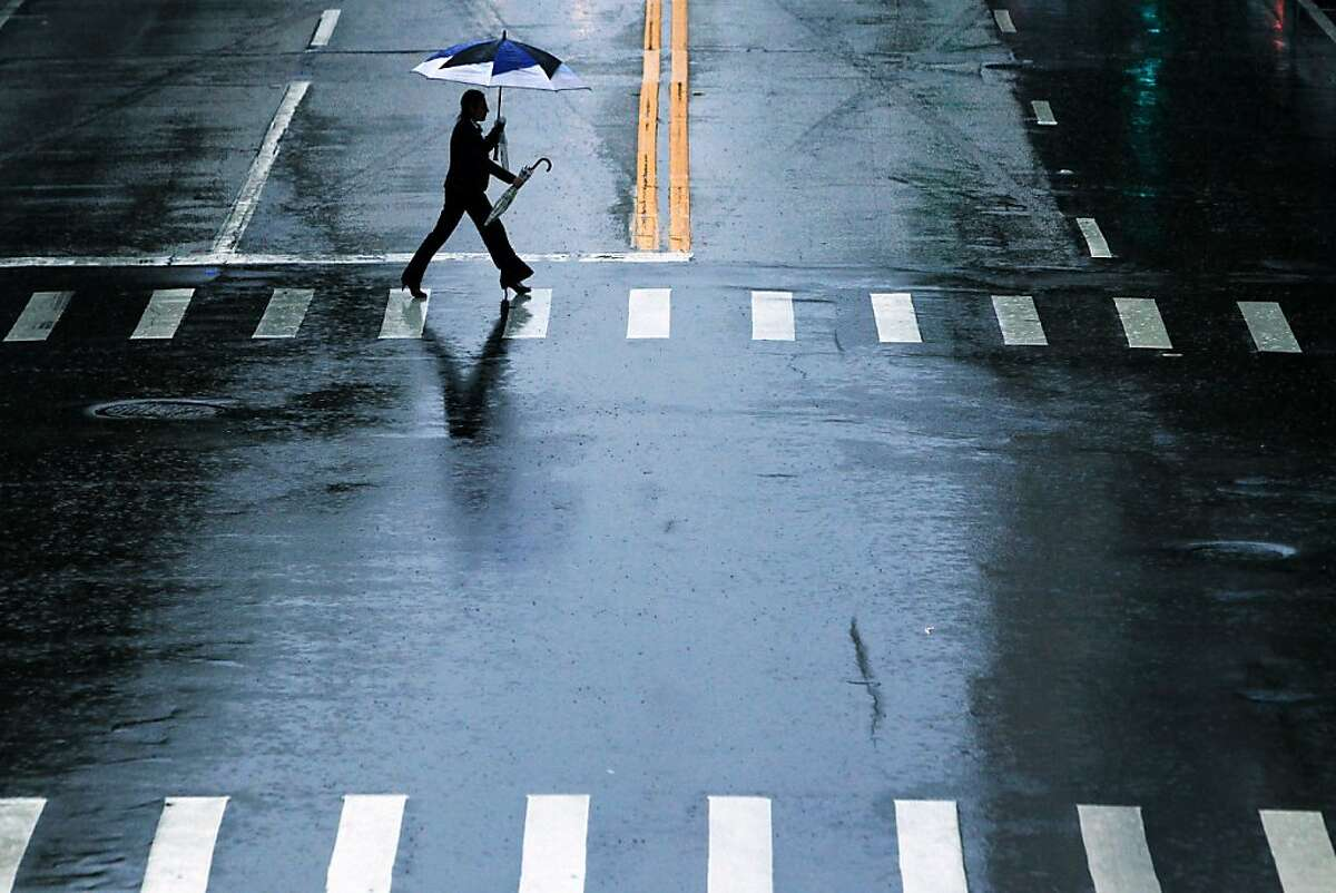 A woman crosses Twiggs Street in Tampa, Fla. during a rain storm on Monday, Sept. 23, 2013. Rain storms doused Tampa Bay for much of the day with wet weather expected to continue through the week. (AP Photo/The Tampa Bay Times, Edmund D. Fountain) TAMPA OUT; CITRUS COUNTY OUT; PORT CHARLOTTE OUT; BROOKSVILLE HERNANDO TODAY OUT