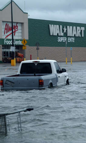 Storm water stands 2- and 3-feet deep in the parking lot of the Silsbee Wal-Mart Saturday.(AP PHOTO/THE BEAUMONT ENTERPRISE, RON FRANCELL) Photo: RON FRANCELL, MBR / THE BEAUMONT ENTERPRISE