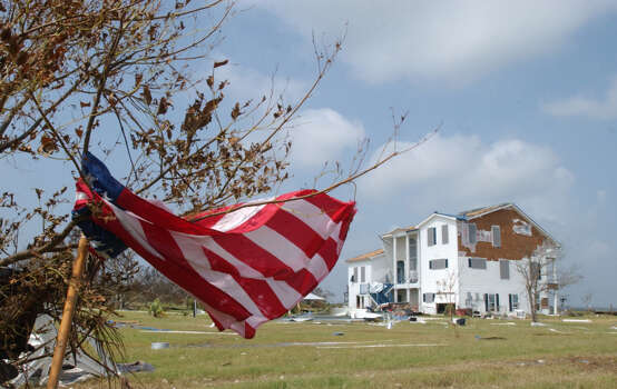 A porch flag is tangled in a tree in front a home severely damaged by Rita on Pleasure Island in Port Arthur, Texas.  Many of the homes on Lake Sabine were damaged by the storm surge.