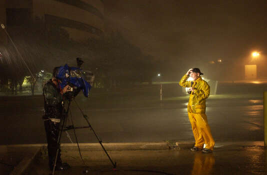 A Television reporter attempts to do a live stand up report around midnight behind the Beaumont Enterprise building as Hurricane Rita's winds blow the Entergy building sign away across the street.(AP PHOTO/BEAUMONT ENTERPRISE, D. RYAN) Photo: DAVE RYAN, ASSISTANT PHOTO EDITOR / &copy The Beaumont Enterprise