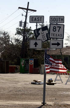 A flag flies from the highway signs at the 4-way stop Wednesday in Sabine Pass. 