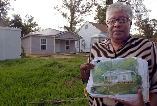 HOUSES102109_2_Cora Mallett holds a picture of her home that is being rebuilt after suffering extensive damage from Hurricane Rita in 2005. The contractor who was rebuilding her home has been fired by the state for substandard work. Pete Churton/The Enterprise