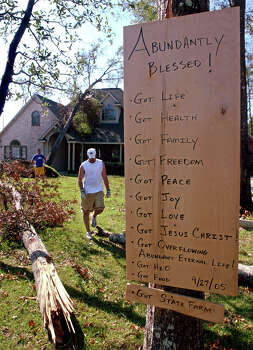 A sign listing blessings hangs in a yard as Greg Owens of McAllen, left, and Jared Best of Silsbee remove hurricane debris in Silsbee on Oct, 3, 2005. Hardin County was one of nine Texas counties designated for Hurricane Rita relief. Enterprise file photo Photo: File / Beaumont