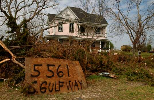 A piece of plywood, proped up by debris, marks the address for the Plummer-Deslatte home in Sabine Pass. The home was damaged by Hurricane Rita.