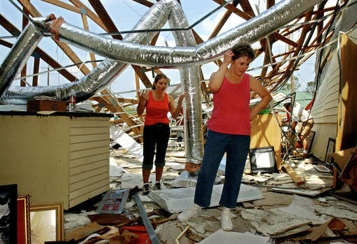 Anita Murchison (cq), owner of The Frame & Art Co. in Bridge City, (center), her daughter Kim Long (left) and son-in-law Philip Long (right) dig through the wreckage at the shop in Bridge City on Tuesday, September 27. Hurricane Rita tore through the Southeast Texas on Saturday, September 24, 2005.