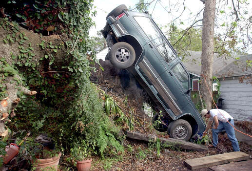 Javier Blas, 20, of Beaumont, Texas, checks out the front end of his Chevy Blazer Tuesday morning in the backyard of his Beaumont home. Hurricane Rita left the SUV in a precarious position more than two weeks ago when she blew through the area. Blas says that beside a little front end damage he thinks the vehicle is driveable. Photo: Scott Eslinger, Staff Photographer / The Beaumont Enterprise