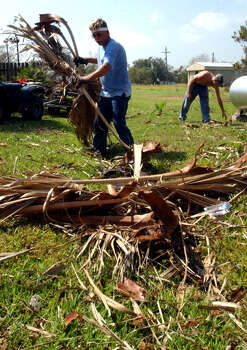 Michael Visoski, left, and Dusty Monroe start cleaning the grounds around the Gulfway Motel Monday September 26, 2005 in High Island, Texas. The motel was not damaged by Hurricane Rita's winds, but the property was littered with palm fronds and other debris.