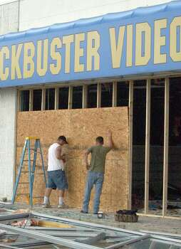 In Orange Wednesday workers nail up plywood to protect the Blockbuster Video store on 16th Street. Hurricane Rita knocked out most of the store's windows and caused heavy damage. (AP PHOTO/THE BEAUMONT ENTERPRISE, KEVIN DWYER) Photo: KEVIN DWYER, MBR /  THE BEAUMONT ENTERPRISE
