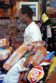 Checker Alfred Bernard, 40, right, of Beaumont, Texas, checks groceries Tuesday afternoon at a Kroger in Beaumont, Texas, for some of the Southeast Texans who either rode out Hurricane Rita or have managed to slip back into the city. The city of Beaumont, Texas, is still closed and authorities in Beaumont and other Southeast Texas cities have pleaded with residents not to try returning home explaining that there will be no power or water service for the next few weeks. Despite this several area stores and gas staions have been reopening on generator power. Photo: Scott Eslinger, AP / The Beaumont Enterprise
