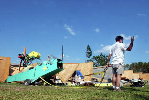 Mike McDonald of Wildwood, Texas, motions to his wife, Wendy McDonald, as she backs their truck up to pull his experimental aircraft, a 1974 Woody Pusher, out of the remains of their storage unit Thursday afternoon, Oct. 6, 2005, in Lumberton, Texas. Hurricane Rita destroyed Colony Mini Storage when the storm battered Southeast Texas. (AP Photo/Beaumont Enterprise, Scott Eslinger) ** MAGS OUT  TV OUT  INTERNET: AP MEMBERS ONLY ** Photo: SCOTT ESLINGER, AP / THE BEAUMONT ENTERPRISE