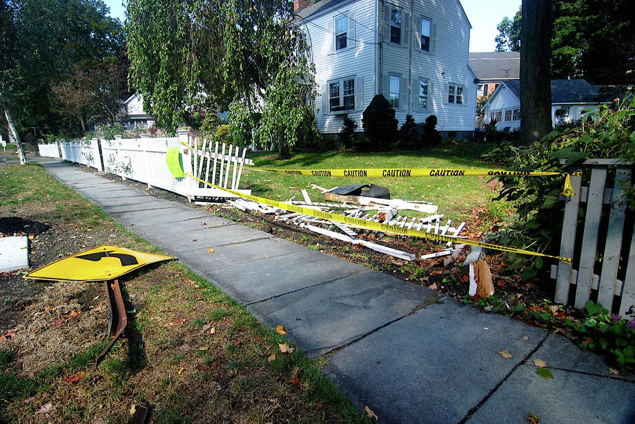 Police are looking for the driver who knocked over a traffic sign and then demolished a section of fence in front of this Pequot Avenue home before fleeing Friday night.  FAIRFIELD CITIZEN, CT 9/20/13 Photo: Contributed Photo / Fairfield Citizen contributed