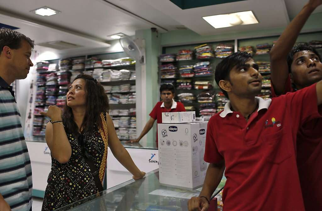 Steve Kowalski (left) and Jennifer Benito-Kowalski buy a bottle sterilizer at a children's store in Anand, India, Thursday, May 23, 2013. Photo: Nicole Fruge, The Chronicle