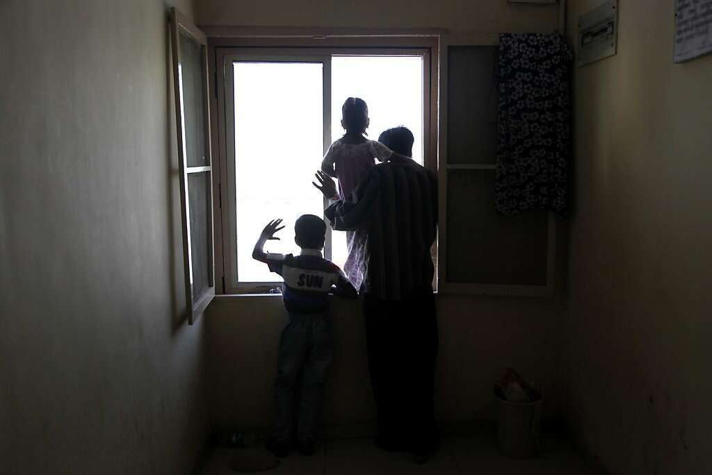 Surrogate Manisha Parmar's husband, Raman (right), daughter, Urvashi, 3, and son, Tanvay, 8, wait in the hall outside her room at the Akanksha Infertility Clinic in Anand, India, Thursday, May 23, 2013.  Parmar gave birth later that day. Photo: Nicole Fruge, The Chronicle