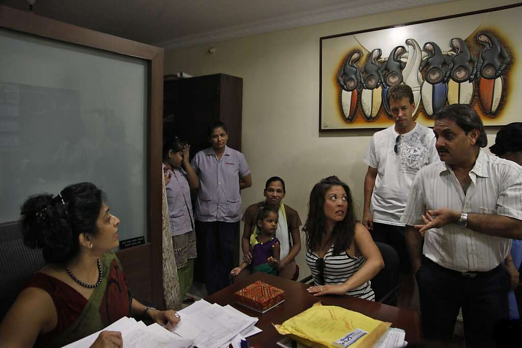 Jennifer Benito-Kowalski (third from right) and Steve Kowalski (second from right) are greeted by Dr. Nayna Patel (left) and her husband, Dr. Hitesh Patel (right) when they arrive at Akanksha Infertility Clinic in Anand, India, Wednesday, May 22, 2013. After years of trying to conceive a child, the Kowalskis paid a surrogate in India to carry their child. Surrogate Manisha Parmar is in the background with daughter Urvashi, 3. It was the first face-to-face meeting between the surrogate and the Kowalskis. Photo: Nicole Fruge, The Chronicle
