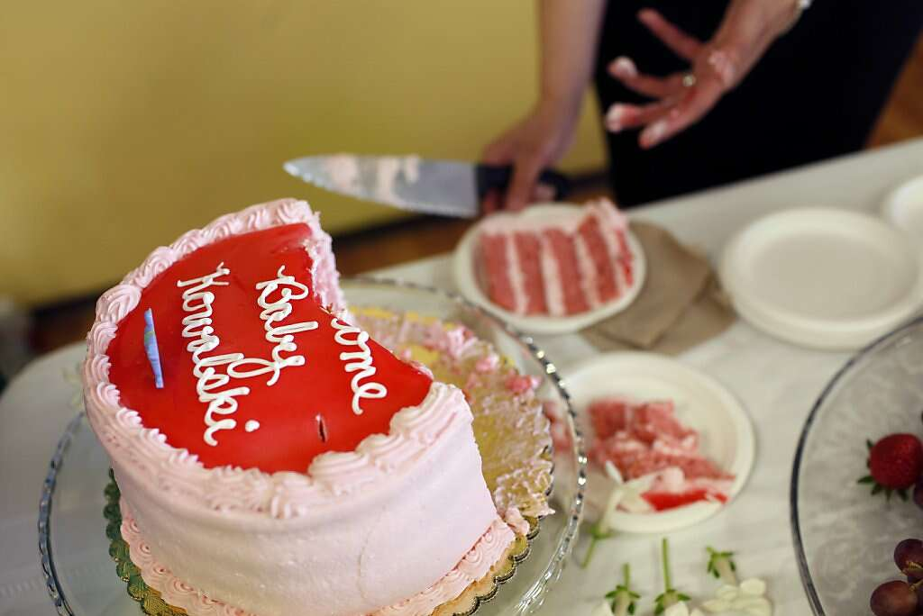 Jennifer Benito-Kowalski's sister Lourdes Benito-Goodall cuts the cake during a baby shower at Fairbrae Swim and Racquet Club in Sunnyvale, Calif., on Saturday, April 6, 2013. After years of trying to conceive, the Kowalskis paid a surrogate in India to carry their child. Photo: Nicole Fruge, The Chronicle