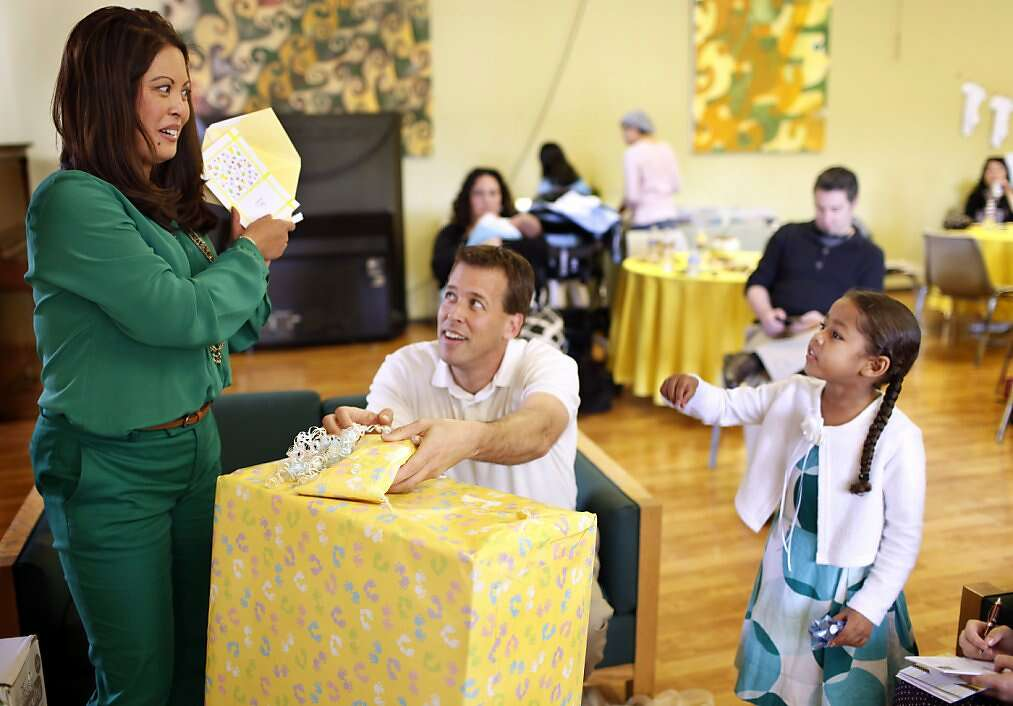 Jennifer Benito-Kowalski (left) and Steve Kowalski open gifts as niece Kiara Walker, 5, looks on during their baby shower at the Fairbrae Swim and Racquet Club in Sunnyvale, Calif., on Saturday, April 6, 2013. After years of trying to conceive, the Kowalskis paid a surrogate in India to carry their child. Photo: Nicole Fruge, The Chronicle
