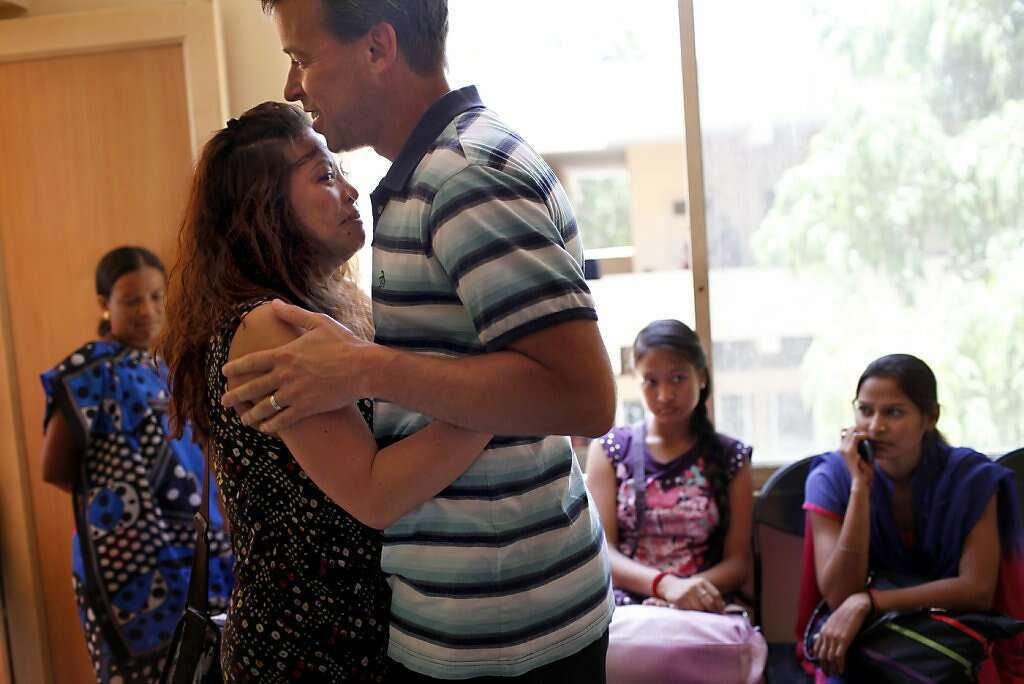 Jennifer Benito-Kowalski and Steve Kowalski embrace after learning that surrogate Manisha Parmar delivered a baby boy by cesarean section at the Akanksha Infertility Clinic in Anand, India, Thursday, May 23, 2013. Photo: Nicole Fruge, The Chronicle