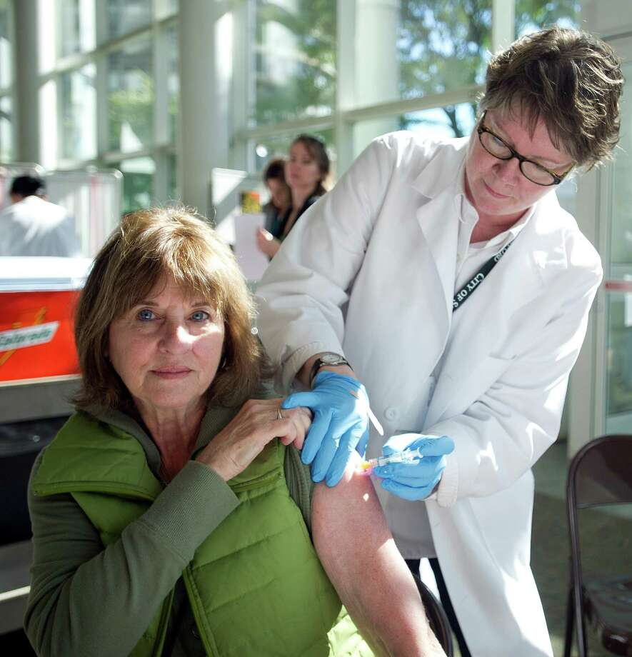 Anita Barkan gets a flu shot from Maryalice Flynn at Government Center on Tuesday, Sept. 24, 2013. Photo: Lindsay Perry / Stamford Advocate